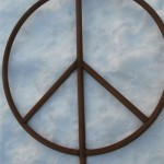 Rusty steel garden peace sign close up in the snow.