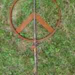 Rusty solid steel garden peace sign sculpture.